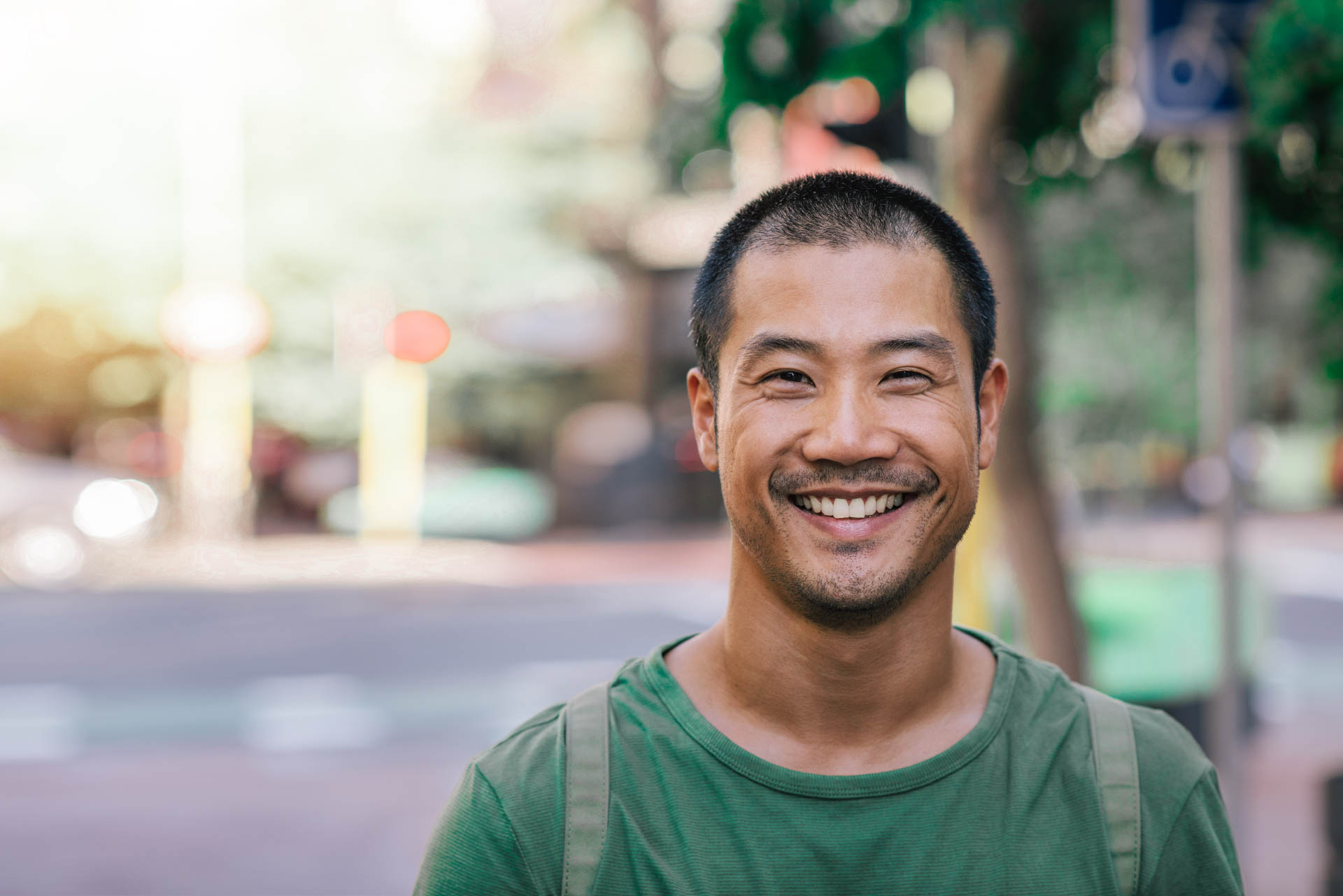 Young Asian man smiling confidently on a city street